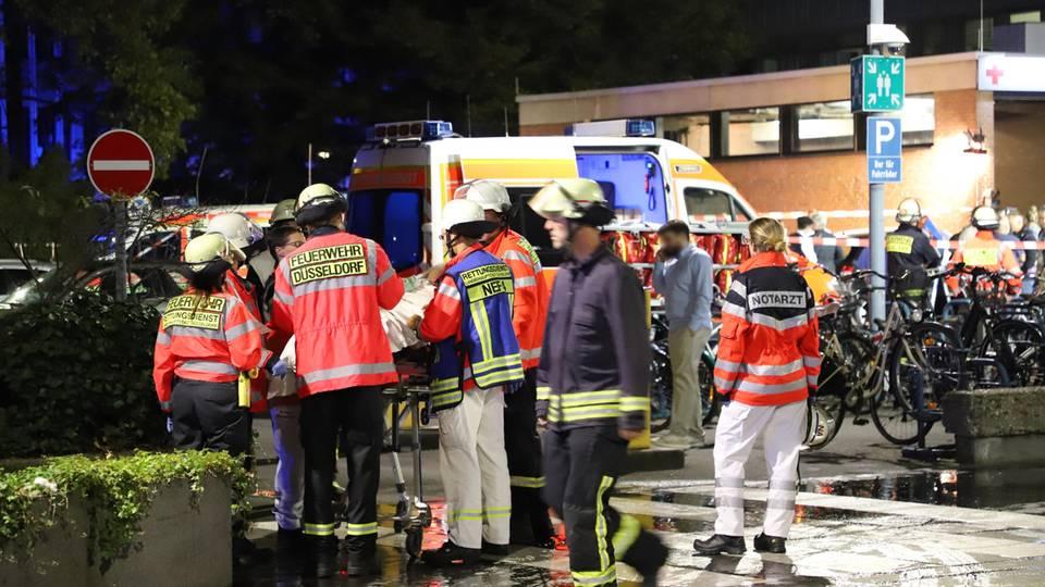 Feuerwehrleute und eine Notärztin stehen nach einem Brand im Marien Hospital um einen Patienten auf einer Liege herum.